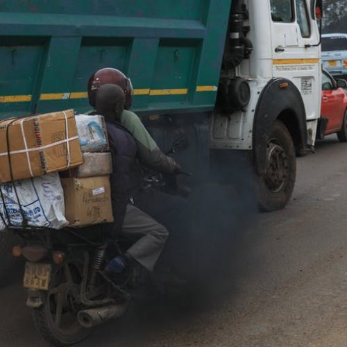 Black exhaust fumes from lorry envelope a motorcyclist and his passenger on a busy road in the Kenyan capital, Nairobi. EPA-EFE/Daniel Irungu