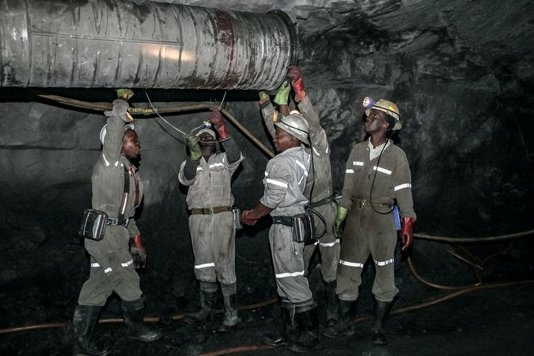 Miners fit a ventilation pipe in an underground platinum mine in South Africa. Shutterstock